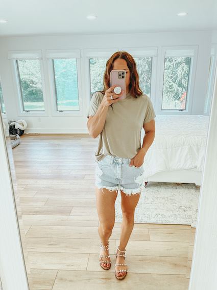woman in distressed shorts - affordable brands at revolve