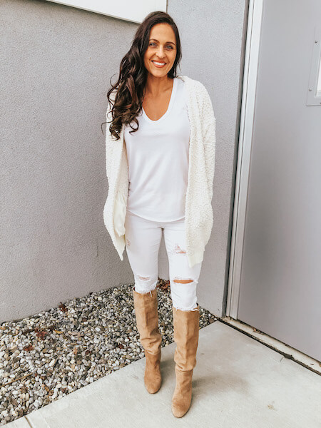 woman wearing white jeans with knee high boots