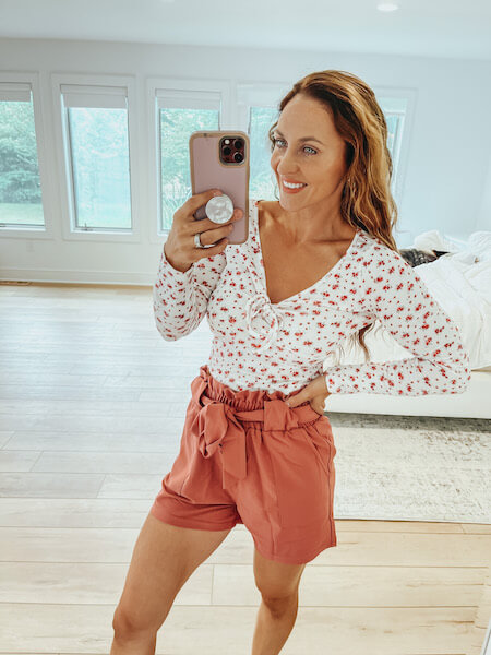 woman wearing a floral top and high waisted shorts