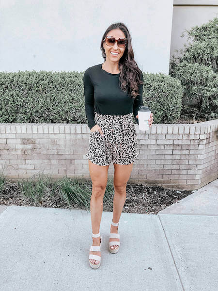 woman wearing leopard paperbag shorts and a black long sleeve bodysuit
