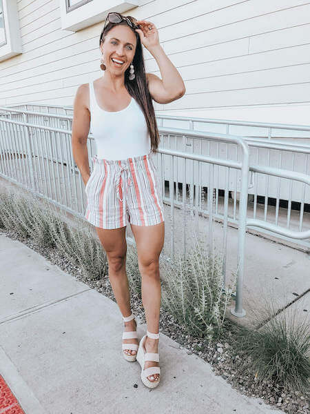woman wearing striped shorts and a white tank top