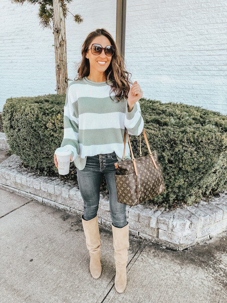woman in green sweater and jeans with knee high boots