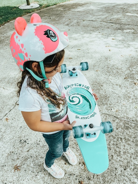 kid holding skateboard - best outdoor gifts for kids